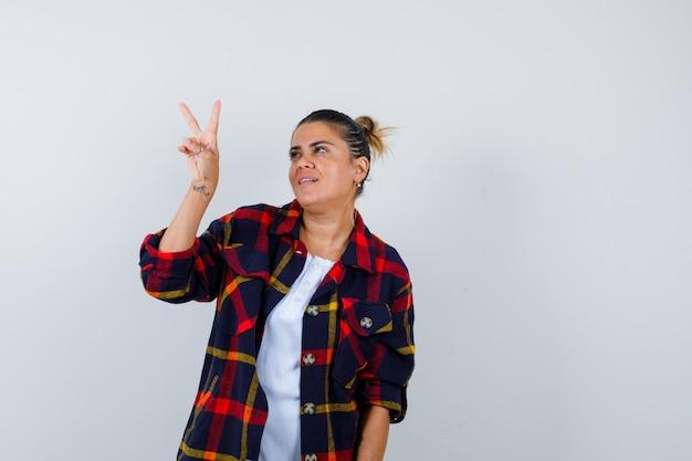 Bella donna che mostra gesto di pace in maglietta bianca, camicia a quadretti e sembra felice. vista frontale.