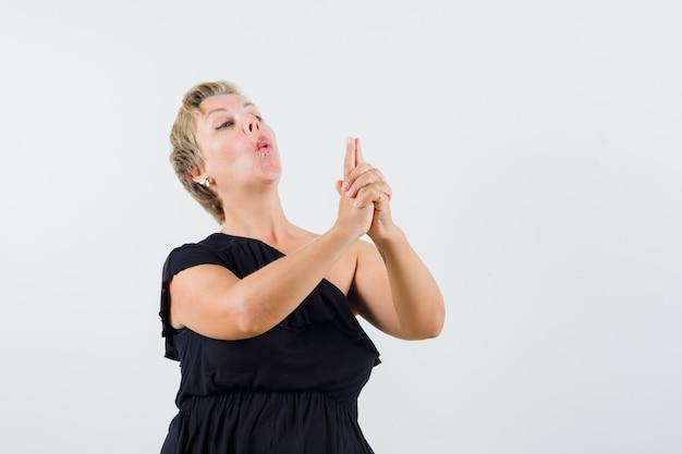 Красивая женщина показывает жест пистолета в черной блузке и выглядит уверенно