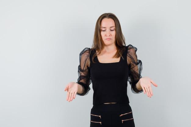 Bella donna che mostra qualcosa in camicetta nera e che sembra insoddisfatta