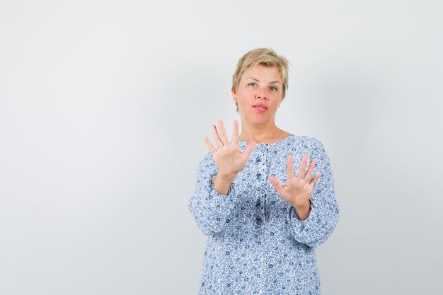Красивая женщина показывает жест остановки в узорной блузке и выглядит сконцентрированным, вид спереди. место для текста