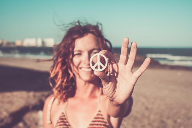 Красивая женщина показывает символ мира на пляже в одиночестве и изолирована с морем и песком пляжа на заднем плане - кавказская девушка улыбается и смотрит в камеру