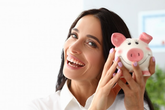 Beautiful woman shows piggy bank and smiles