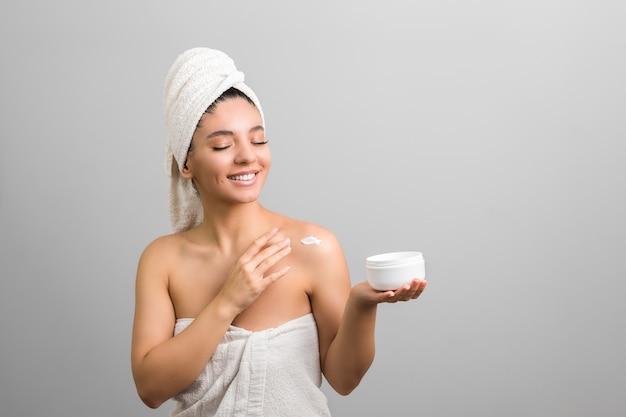 元気にクリーム色の白い瓶を押しながら体に触れるタオルに包まれた美しい女性