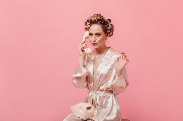 Bella donna in vestaglia di seta civettuola parlando al telefono sulla parete rosa