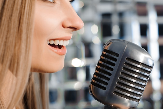 Beautiful woman singing on the stage next to the microphone.