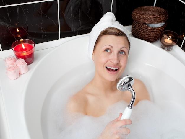 Beautiful woman singing while having a bath