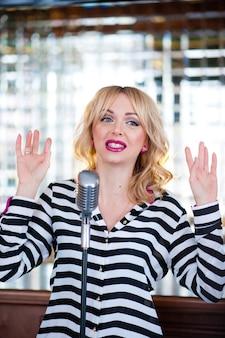 Красивая женщина поет с микрофоном