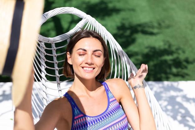 Beautiful woman sit on backyard chair at summer sunny day enjoying amazing warm weather, catching sun rays