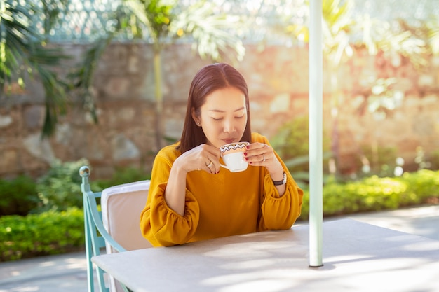 Beautiful woman sit on the table drinking coffee in cafe outdoor in the garden.