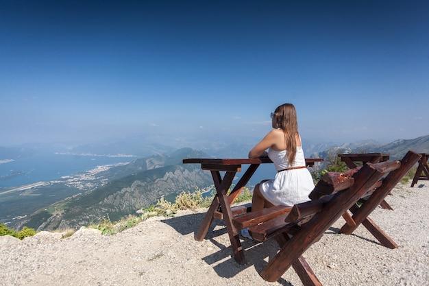 Красивая женщина сидит на скамейке на вершине горы и смотрит на пейзаж