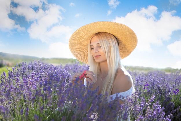 Красивая женщина сидит в поле лаванды