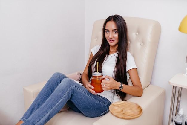 Красивая женщина сидит и пьет чай