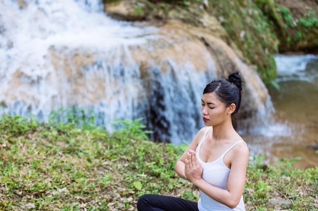 앉아서 요가 연습하는 아름 다운 여자.