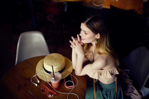 카페 커뮤니케이션에서 음료를 마시며 테이블에 앉아 있는 아름다운 여성