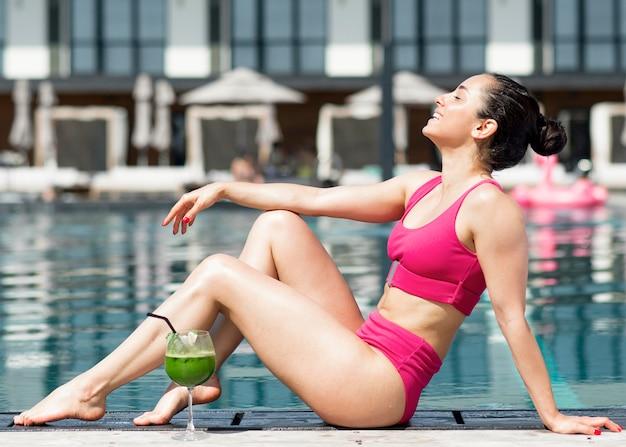 Красивая женщина, сидя у бассейна