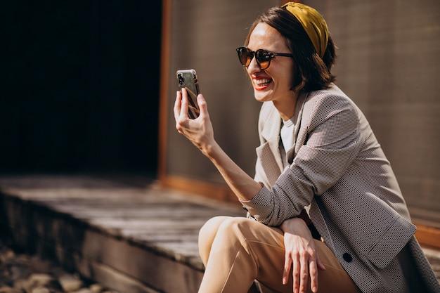 Bella donna che si siede nel cortile e usando il telefono