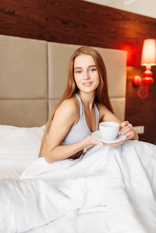 Beautiful woman sitting in the bed with cup of coffee, good morning. girl wake up in bedroom