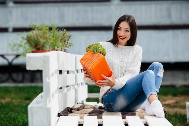 Bella donna seduta su una panchina e tenendo tra le mani un regalo