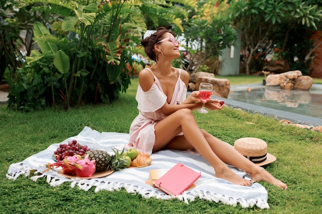 Beautiful woman sitting on blanket, drinking wine and enjoying summer picnic in tropical garden.