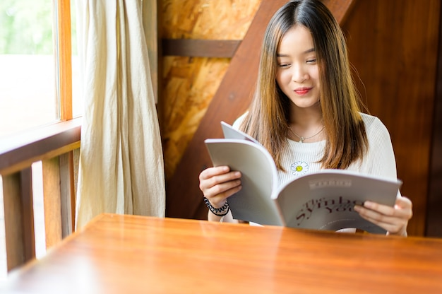 Beautiful woman sitting in a cafe reading a magazine