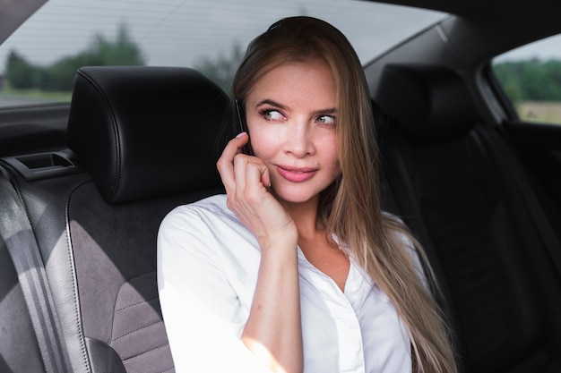 Beautiful woman sitting in the car and looking away