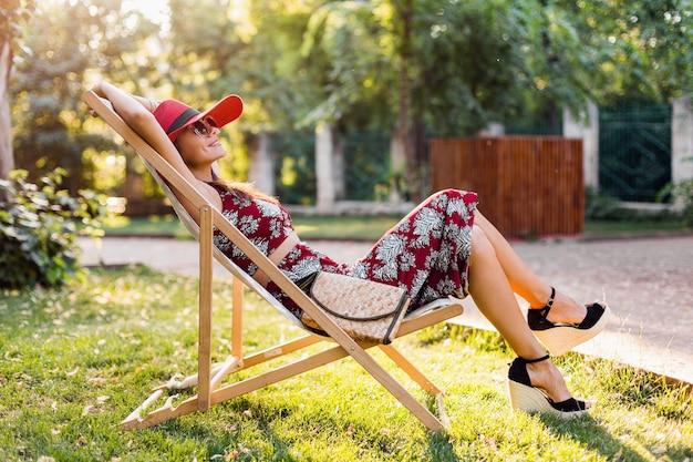 熱帯の衣装でデッキチェアに座っている美しい女性。ストリートスタイルの夏のファッショントレンドの女性。わらのハンドバッグ、赤い帽子、サングラスを身に着けています。休暇中に幸せな気分で笑っているスタイリッシュな女の子。
