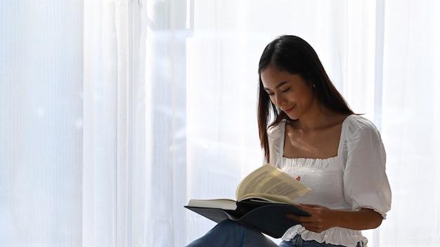 Красивая женщина, сидя в гостиной и читая книгу на выходных.