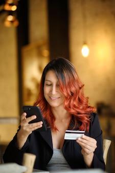 Сидящая красивая женщина смотрит на свой мобильный телефон, держа в руке кредитную карту