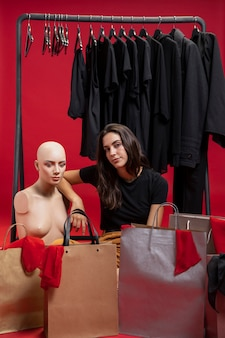Beautiful woman sitting next to mannequin