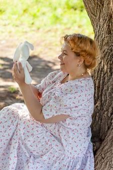 야외에서 나무 근처에 앉아 아름 다운 여자. 여름 공원에서 낭만적인 소녀입니다. 로맨틱한 이미지