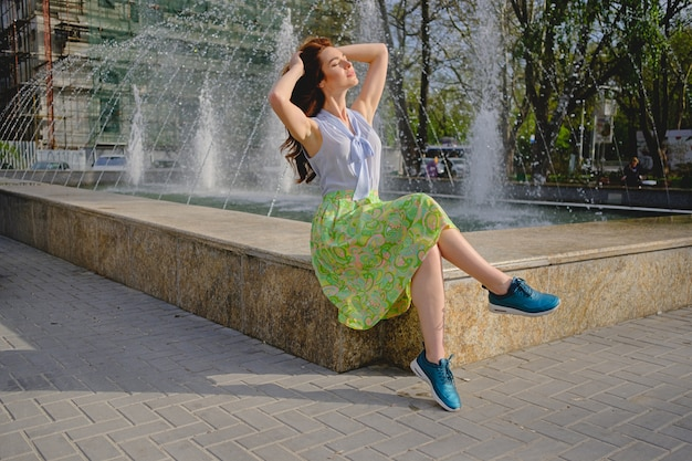 Beautiful woman sitting near fountain