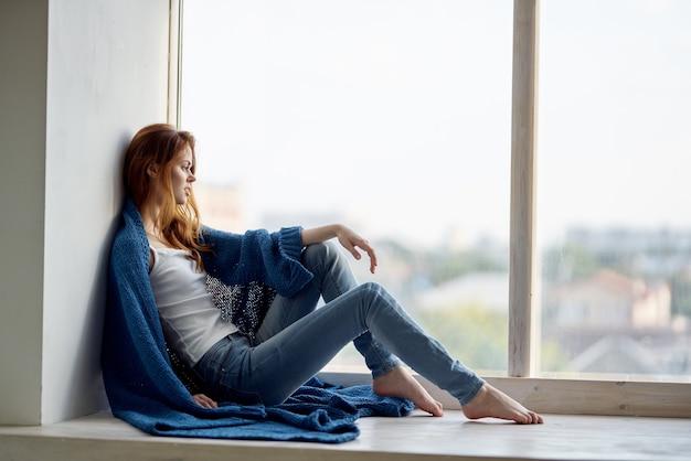 青い格子縞の休息と窓の近くに座っている美しい女性