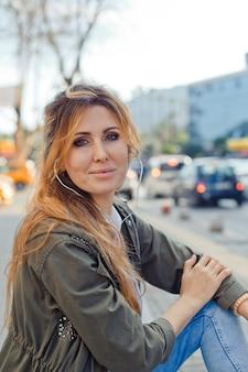 少し笑顔で昼間に通りで音楽を聴くベンチに座っている美しい女性