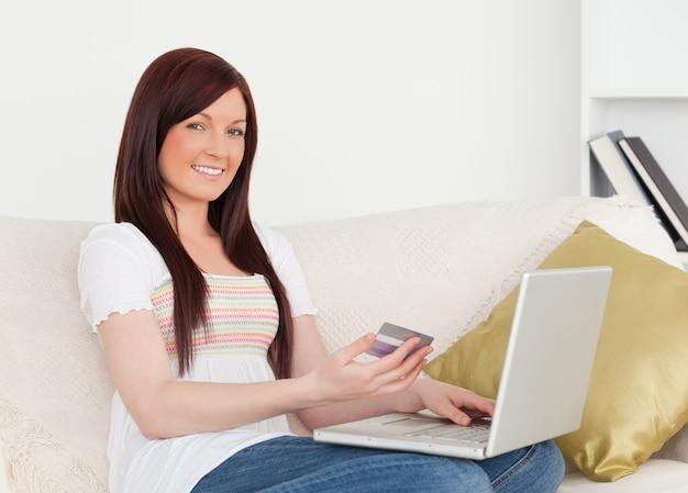 ソファに座っている美しい女性は、インターネットで支払いをするつもりです
