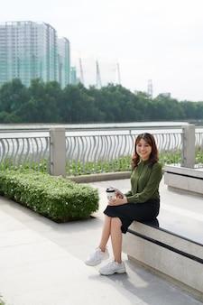 屋外のテイクアウト コーヒーのカップを保持しているベンチに座っている美しい女性。