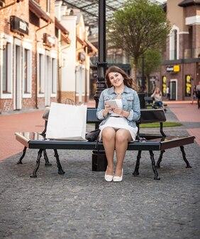 買い物袋を持ってベンチに座り、タブレットを使う美しい女性