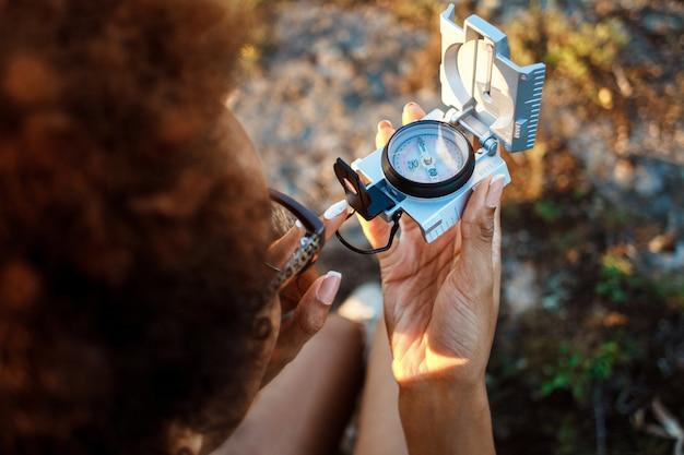 Красивая женщина, сидя на скале в каньоне, глядя на компас