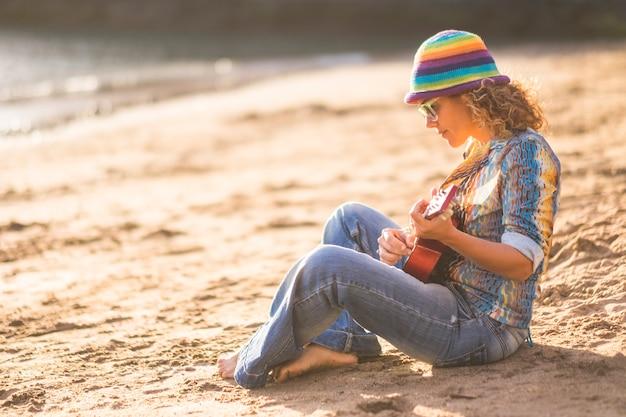 해변에서 모래에 앉아서 기타를 연주하는 아름 다운 여자. 휴가 기간 동안 해변에 앉아 기타를 연주하는 모자와 선글라스를 쓴 세련된 여성의 프로필