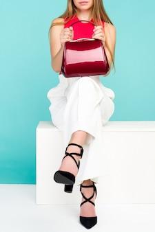 Красивая женщина, сидя на скамейке с красным кошельком и туфлями на высоком каблуке.