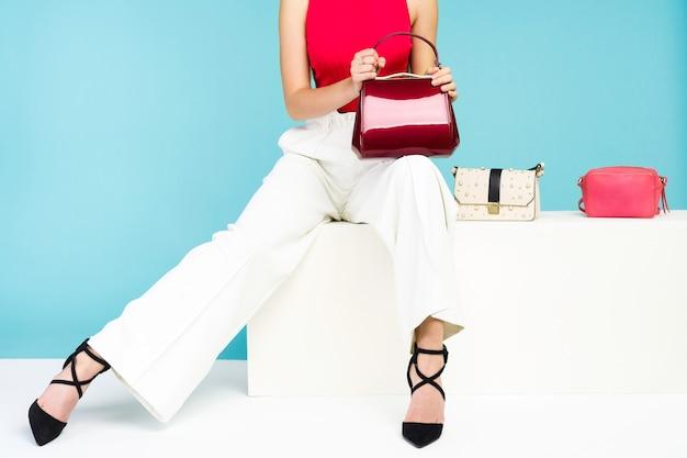 Красивая женщина, сидящая на скамейке с тремя сумочками и туфлями на каблуках