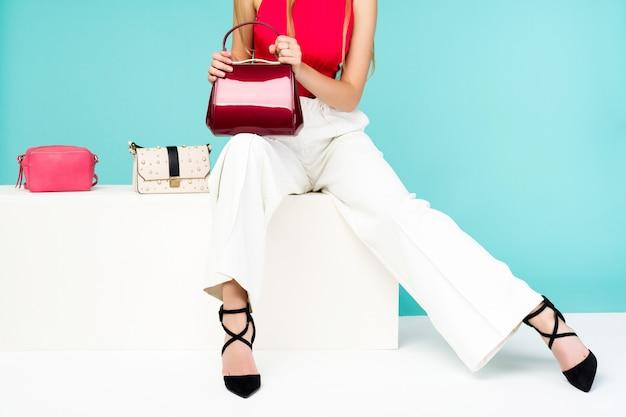 벤치에 앉아 아름 다운 여자입니다. 핸드백 지갑 3 개와 하이힐 신발.