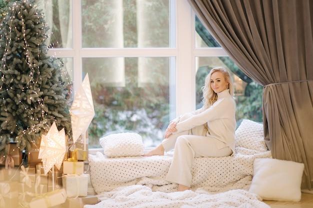 크리스마스 트리 창턱에 앉아 아름 다운 여자입니다. 흰색 의상에 금발 머리 여자는 나머지