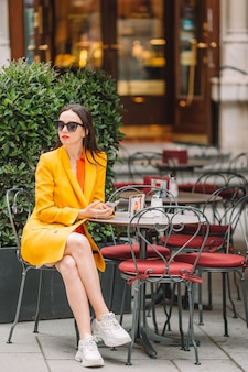 Beautiful woman sitting in outdoors cafe at european city