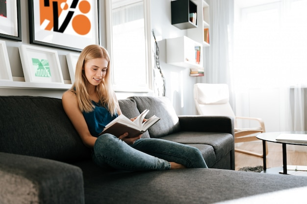 Beautiful woman sitting and reading book at home