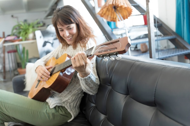 Beautiful woman sitting on a sofa and  playing guitar