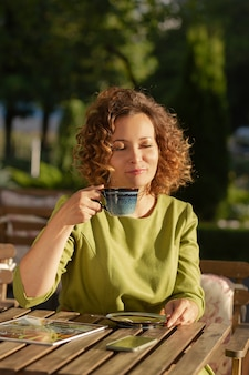 The beautiful woman sitting in a summer cafe drinking coffee