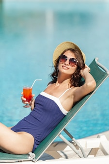 Beautiful woman sitting on sunbed a cocktail