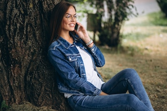 Beautiful woman sitting under a tree and talking on the phone