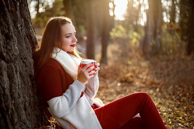 手にグリューワインのカップと木の下に座っている美しい女性。