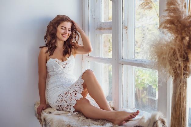 Beautiful woman sitting on the windowsill